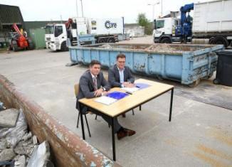 Frans van Strijp (links) en Machiel van Haaften ondertekenen de overeenkomst op de milieustraat in Eindhoven