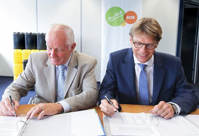 Dhr C. Houweling (l) en Dhr W. Droogh (r) tekenen een samenwerkingscontract.